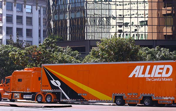 Corporate movers getting ready with Allied Van Lines moving truck in front of office building
