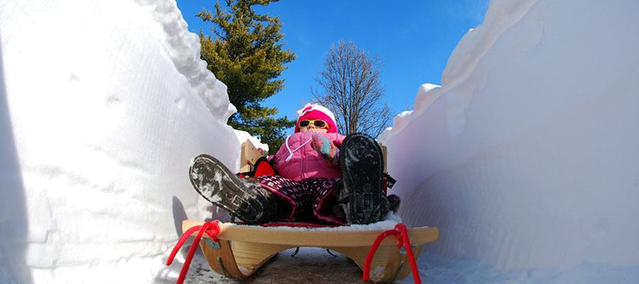 Moving in Winter in Minnesota? Here are tips to make your winter move more enjoyable. Little girl on sled having fun in snow while parents get ready for moving to Minneapolis.